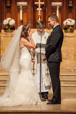 Bride and groom standing with pastor in chapel