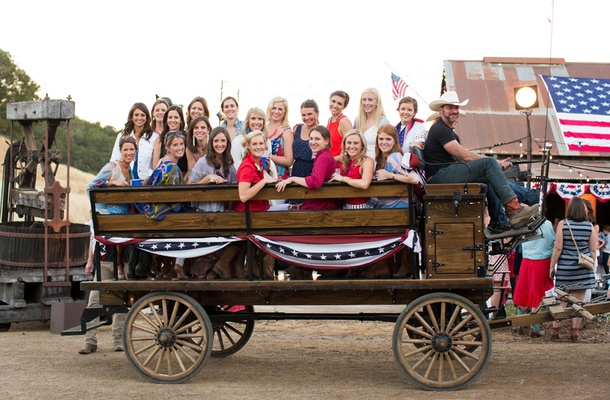 Guests pose for photo in old fashioned wooden wagon