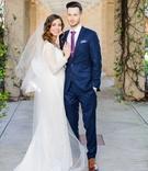 Newlyweds in wedding attire under atrium
