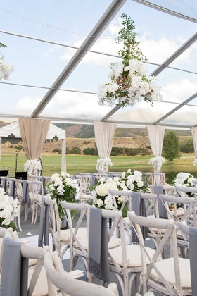 Whitewash wood chairs with grey blankets on back antler greenery flower chandelier ranch venue tent