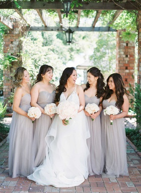 bride in v neck hayley paige wedding dress with bridesmaids in strapless light grey taupe gowns