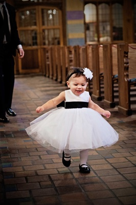 adorable little girl toddler in a black and white dress with a flower headband runs through church