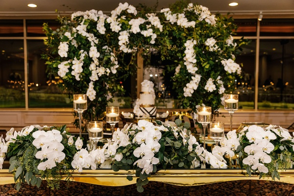 wedding cake four layer geometric design under ceremony arch greenery orchid gold sweetheart table
