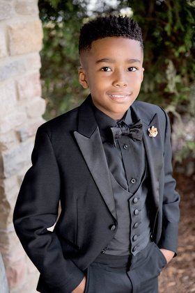 Young ring bearer posing for photo in tuxedo black jacket vest shirt and bow tie slacks