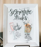 Framed signature drink sign with drawings of drink and calligraphy champagne and bourbon