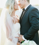 bride in galia lahav groom in men's wearhouse about to kiss long veil