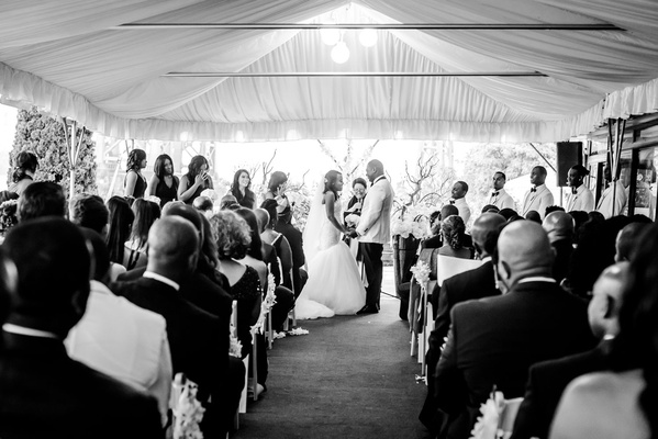 Black and white photo of tent wedding ceremony African American couple