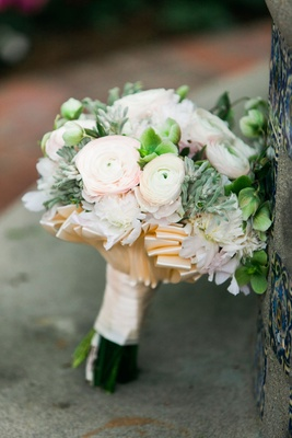 Bridal wedding bouquet with greenery verdure pink ranunculus flowers and champagne ribbon
