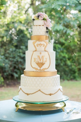 ornate, regal wedding cake with gold details and fresh flowers