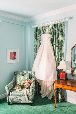 Off the shoulder blush ball gown wedding dress hanging up in bridal suite at the colony palm print