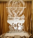 Ice sculpture at wedding reception with fleur de lis, monogram, and bluebonnets