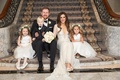 Bride in Inbal Dror wedding dress with groom in tuxedo and little ring bearer flower girls flowers