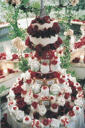 display of mini white cakes decorated with red roses