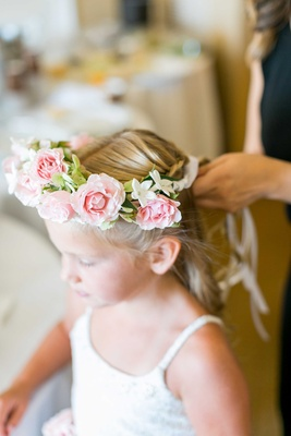 Flower girl in white lace dress with pink rose flower crown getting hair done for wedding
