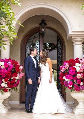 wedding portrait under archway at beverly hills private home urns filled with bright pink flowers
