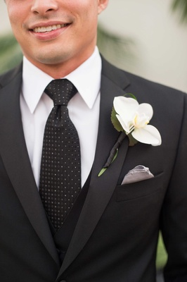Man in black and white tie with single flower on lapel