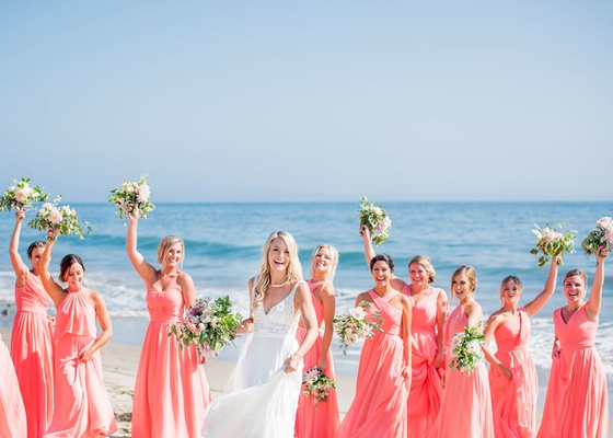 wedding portraits of bride and bridesmaids mismatched coral pink bridesmaid dresses ocean
