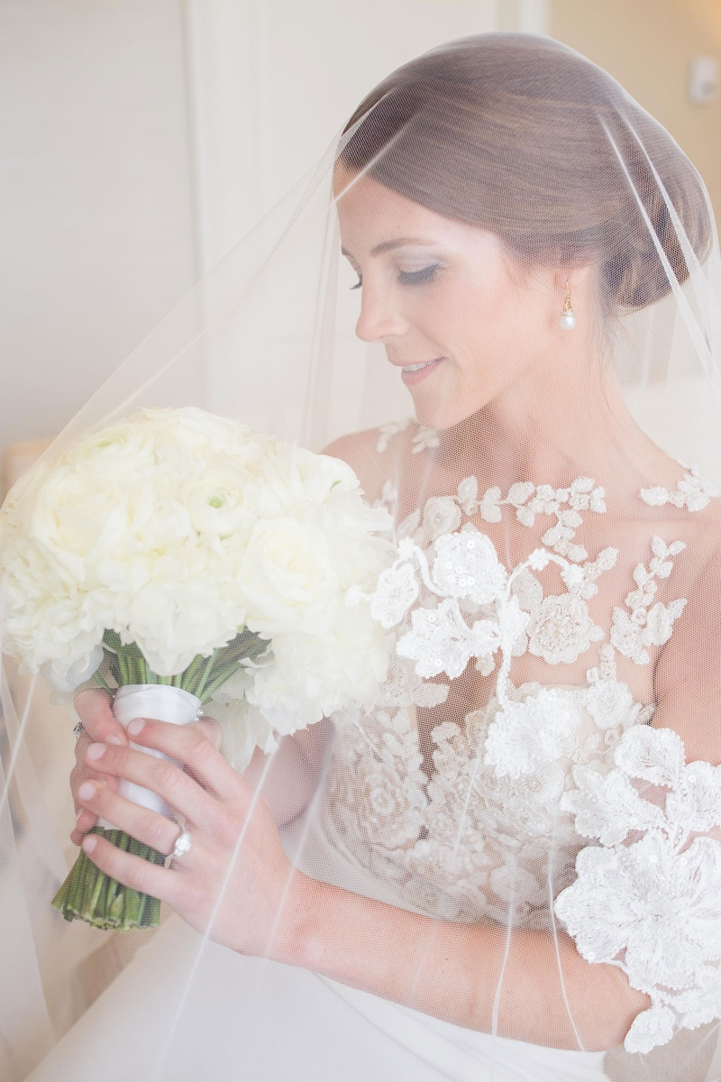 bride in pronovias atelier wedding dress with blusher veil over head, ivory bridal bouquet