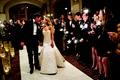 Bride and groom walk up aisle as guests wave sparklers