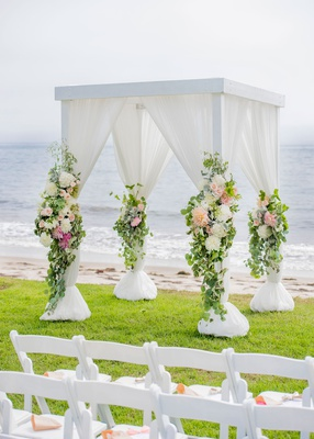 wedding ceremony on grass lawn by beach ocean white drapery greenery peach pink flowers dahlia rose