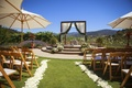 Outdoor Jewish wedding ceremony at Holman Ranch with white petals along the aisle, umbrellas