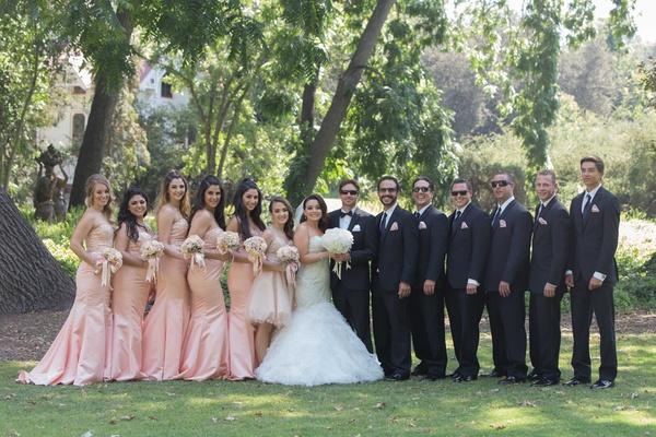 Bride in mermaid wedding dress with groom in tux sunglasses, pink bridesmaid dresses, groomsmen suit