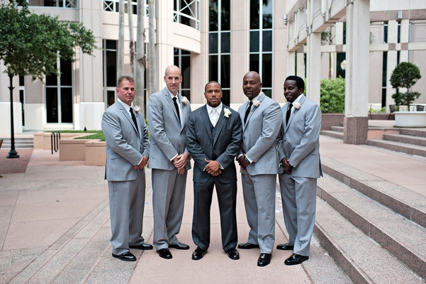 Groom in three-piece suit with diverse groomsmen