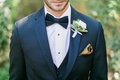 Groom suit with bow tie, patterned pocket square, and white flower boutonniere