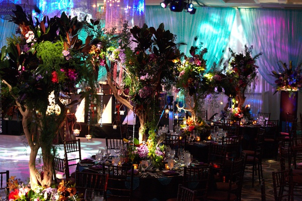 centerpieces made with trees, flowers, and peacock feathers