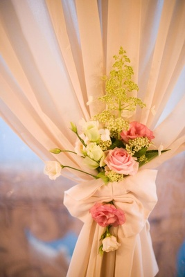 Green plant and pink rose flowers on ivory drapes