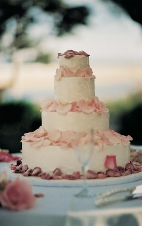 Four tiers with white frosting and pink petals