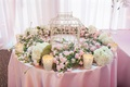 Round table decorated with fresh flowers and birdcage