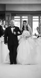 Black and white photo of bride walking down aisle with father
