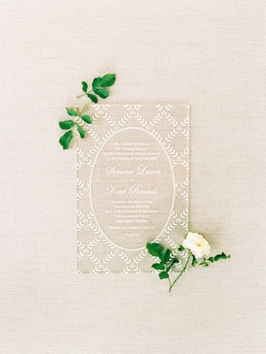 lucite acrylic clear translucent wedding invitation with white script and lace design from dress