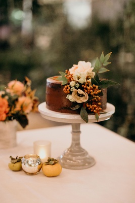 wedding cake small on cake stand chocolate frosting white flowers greenery orange berries
