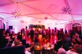 Supper club theme wedding reception with guests on dance floor under retro style light fixtures