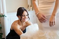 smiling bridesmaid in black dress helps bride into her mermaid style wedding dress