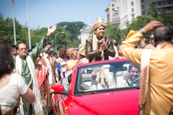 Indian groom rides in red convertible during the baraat