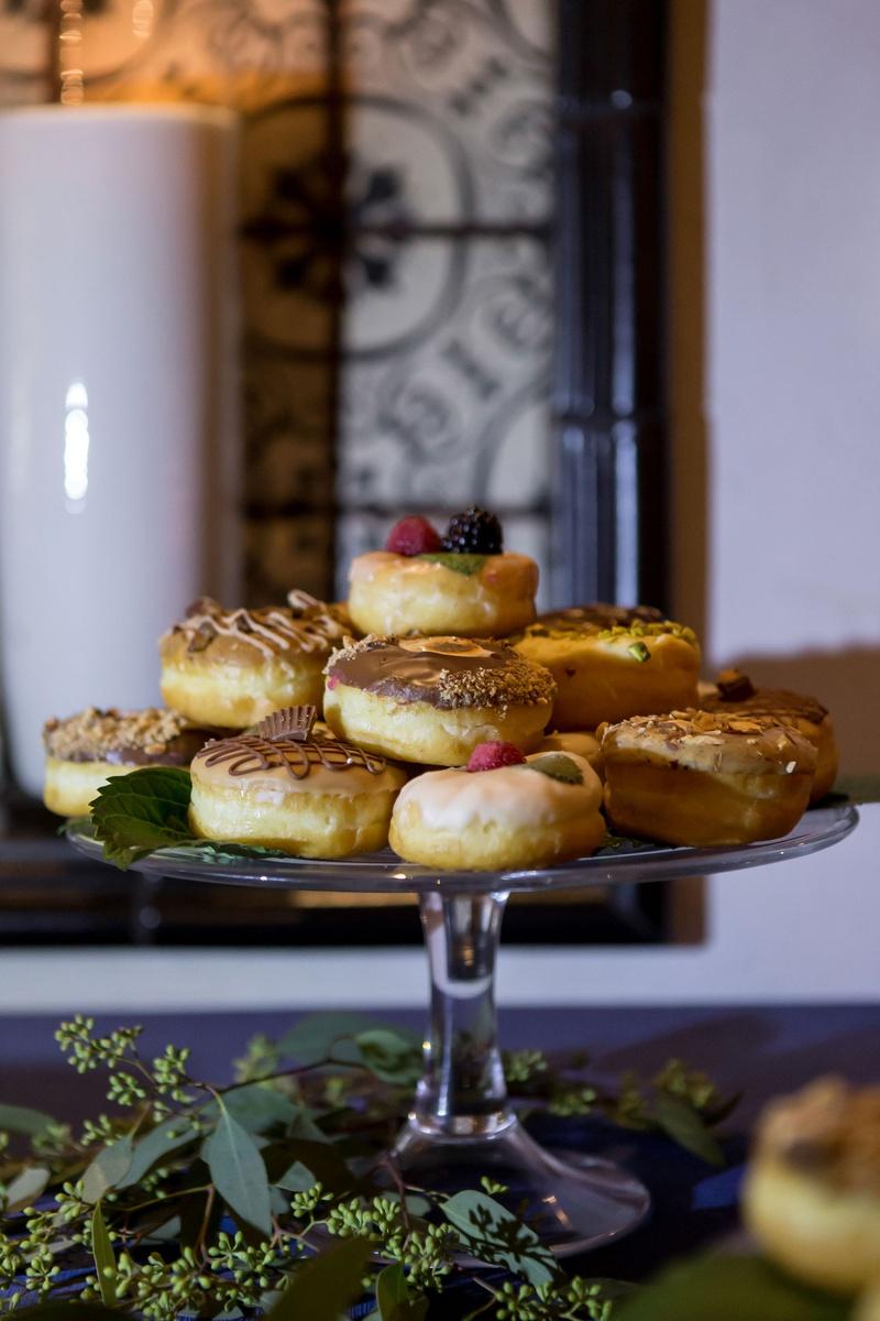 wedding reception donuts doughnuts on glass cake stand greenery