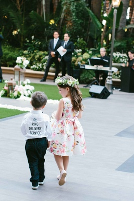 "Ring bearer in ""Ring Delivery Service"" button up shirt and flower girl in flower crown floral dress"