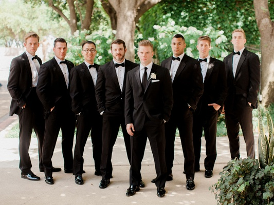 Groomsmen in suits and bow ties and groom in regular tie white boutonniere