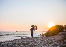 wedding portrait santa barbara beach in california destination wedding kiss sunset cotton candy sky