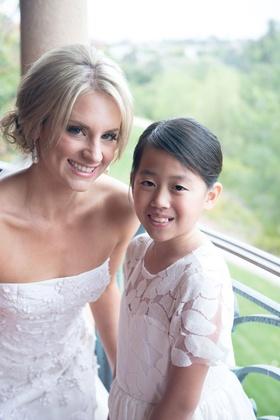 Bride in strapless oscar de la renta wedding dress updo with flower girl in updo and white dress