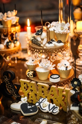 dessert table with small desserts on tiers of cake stand, bride and groom's names with wedding date