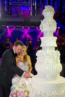 Bride and groom cut seven foot tall wedding cake