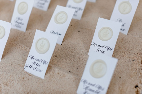 destination wedding tropical beach decor escort cards calligraphy wax seal in sand