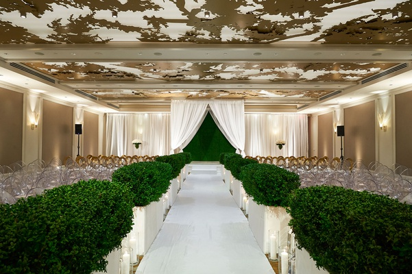 wedding ceremony ballroom gold ceiling hedge along aisle hedge wall backdrop white drapery