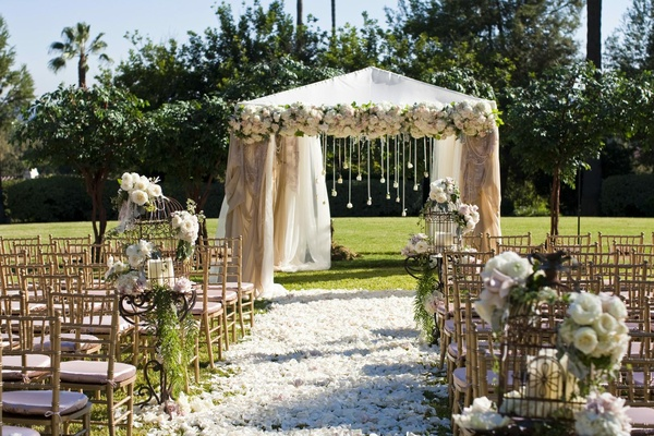 Outdoor wedding with gold chairs and neutral colors