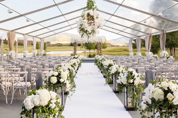 Open side clear tent wedding ceremony ranch aspen colorado white flowers antlers decor lanterns