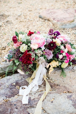large bridal bouquet in shades of pink, burgundy, purple, and yellow accents